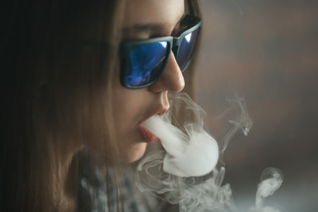 Vape. Young handsome white girl in sunglasses is admiting puffs of steam from the electronic cigarette. Vaping. Teenager. Stock Photo