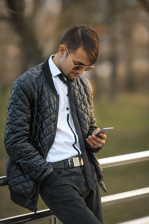 Gadget man with mobile phone. Portret of a handsome young white guy with modern haircut in aviator sunglasses posing with smartphone at sunset. Lifestyle.