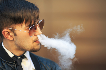 joven fumando: Vape man. Portrait of a handsome young white guy with modern haircut in aviator sunglasses vaping an electronic cigarette opposite the futuristic urban background. Lifestyle. Foto de archivo