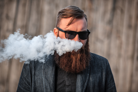 Vape man. Outdoor portrait of a young brutal white guy with large beard and in sunglasses letting puffs out of steam from an electronic cigarette opposite the old wooden fence in the village. Vaping. Stock Photo
