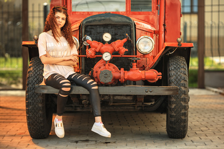 Vintage firefighting truck and pretty teenager. Outdoor portrait of a beautiful young white girl with red curly hair and in black ragged jeans posing near old fire engine. Stock Photo