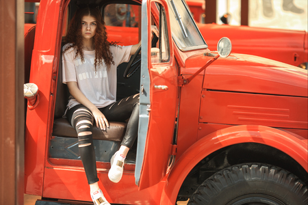 Vintage firefighting truck and pretty teenager. Outdoor portrait of a beautiful young white girl with red curly hair and in black ragged jeans posing behind the wheel of the old fire engine.