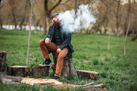 joven fumando: Vape man. Photo of a brutal bearded young man having rest after chop firewood and vaping an electronic cigarette in the village. Lifestyle. Foto de archivo
