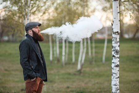 Vape man. Outdoor portrait of a young brutal white guy with large beard and in a vintage cap letting puffs out of steam from an electronic cigarette in the birch grove in the village. Vaping process.
