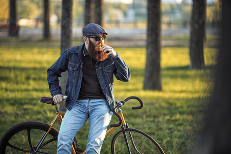 Vape in real life. Young man with gourgeous large beard and in sunglasses and in the cap having a rest and vaping an electronic cigarette near vintage fix bicycle after ride in the city park. Stock Photo