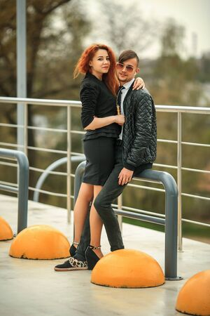 Couple in love. Modern haircuts. Handsome guy in headphones and pretty girl with e-cigarette posing on the urban car parking.