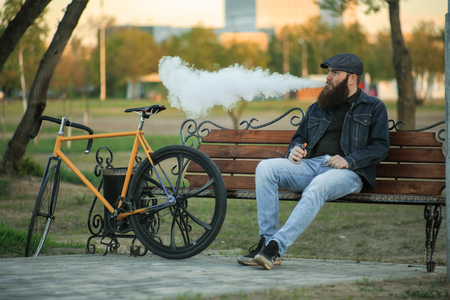 Vape in life. Young man with gourgeous large beard in sunglasses and in the cap having a rest and vaping an electronic cigarette near vintage fix bicycle after ride on the bench in the city park. Stock Photo