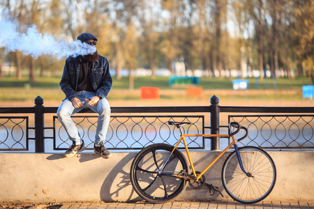 Vape in real life. Young man with gourgeous large beard and in sunglasses and in the cap having a rest and vaping an electronic cigarette near vintage fix bicycle after ride on the waterfront.