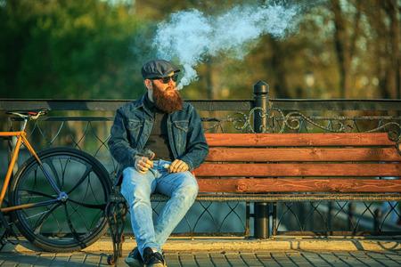 Vape dans la vie. Jeune homme avec une grande barbe gourmande dans des lunettes de soleil et dans la casquette en se reposant et en vapotant une cigarette électronique près d'une bicyclette vintage après avoir roulé sur le banc dans le parc de la ville. Banque d'images - 78920399