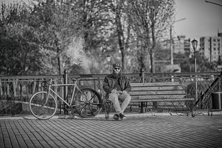 Vape in life. Young man with large beard in sunglasses and in the cap having a rest and vaping an electronic cigarette near vintage fix bicycle after ride on the bench in city park. Black and white.