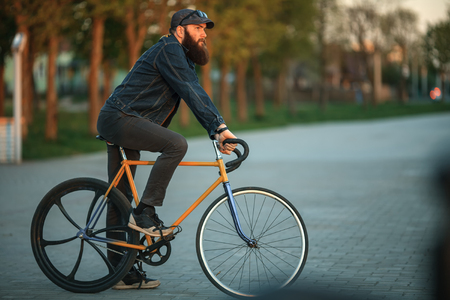 Bearded guy and fix bike. Young man with gourgeous large beard in sunglasses and in the cap riding a vintage bicycle in the city park at sunset. Stock Photo