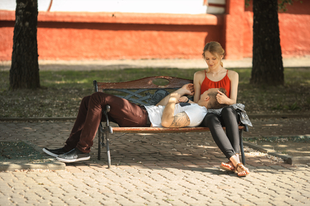 Young modern couple falling in love on the bench at summer day. Stock Photo