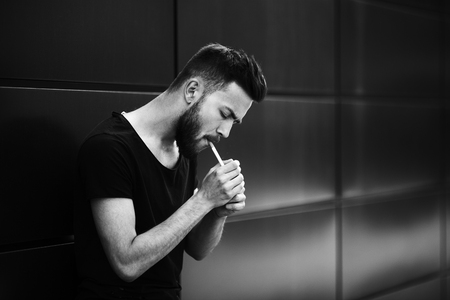 A young handsome white bearded man in black t-shirt smokes a cigarette in the street in the spring. Close up. Black and white. 写真素材
