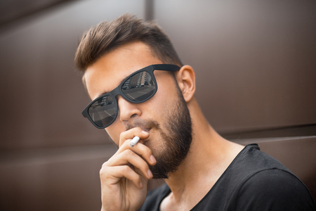 A young handsome white bearded man in sunglasses and black t-shirt smokes a cigarette in the street in the spring. Close up.