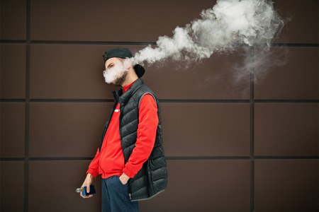 Vape teenager. Young handsome bearded white man in black cap smoking an electronic cigarette and letting off the steam opposite the modern brown background in autumn.