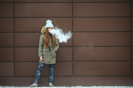 Vape teenager. Young pretty white girl smoking an electronic cigarette opposite modern brown background on the street in the winter.