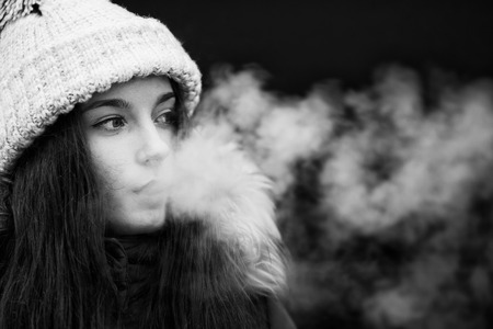 Vape teenager. Young pretty white girl smoking an electronic cigarette opposite modern background on the street in the winter. Bad habit. Close up. Stock fotó
