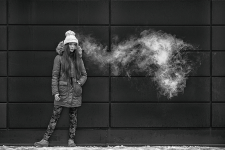 Vape teenager. Young pretty white girl smoking an electronic cigarette opposite modern background on the street in the winter. Bad habit.