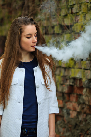 Vape teenager. Young pretty white girl in white cardigan smoking an electronic cigarette opposite destroyed brick wall on the street in the spring. Bad habit. Stok Fotoğraf