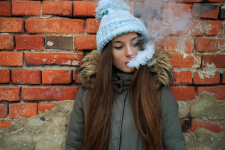 Vape teenager. Young pretty white girl in blue cap and green jacket smoking an electronic cigarette opposite brick wall on the street in the spring. Bad habit. Stock fotó