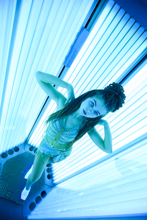 Solarium. Young pretty girl with african braids in a dress for oriental dances sunbathing in a vertical sunbed. Blue neon glow.