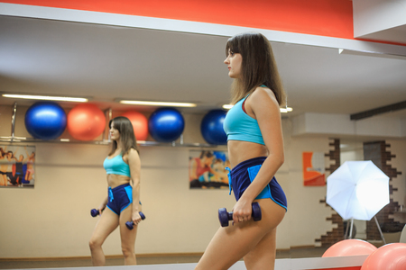 A young beautiful girl with dumbbells in her hands is standing in front of a mirror in a fitness center.