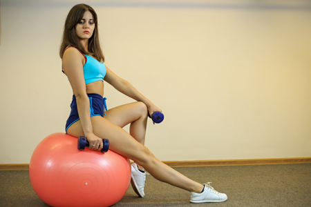 Young beautiful girl is sitting on fitball with dumbells in her hands in a fitness center.
