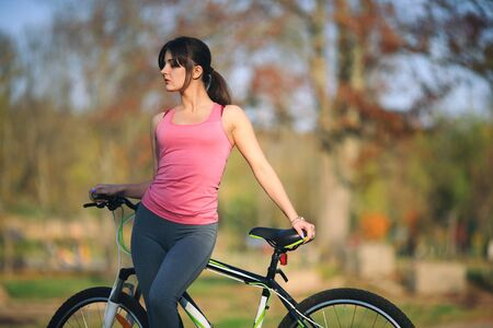 Young beautiful girl in sportswear stands next to a bicycle on the street in the park in autumn. Banque d'images - 133007912