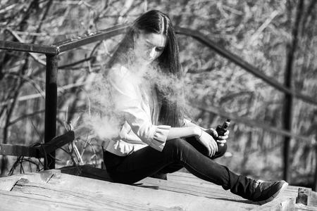 Vape teenager. Young pretty white girl in casual clothing smoking an electronic cigarette on the old wooden stairs on the street in the spring. Bad habit. Vaping activity. Black and white.