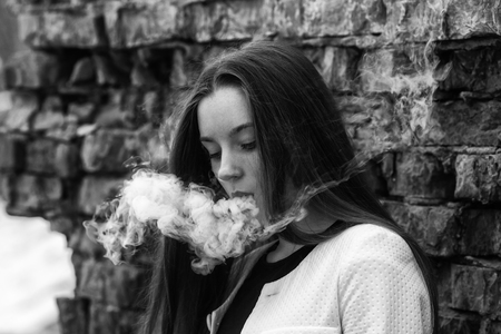 Vape teenager. Young pretty white girl in white cardigan smoking an electronic cigarette opposite brick wall on the street in the spring. Bad habit.  Black and white. Banco de Imagens - 124346808