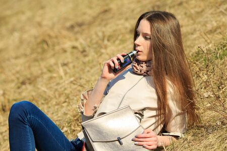 Vape teenager. Young pretty white girl in casual clothing smoking an electronic cigarette on the hillside on a sunny day in the spring. Bad habit. Vaping activity. 免版税图像