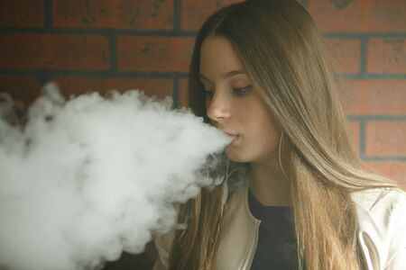 Vaping teenager. Young pretty white girl smoking an electronic cigarette in vape bar. Bad habit. Stock Photo