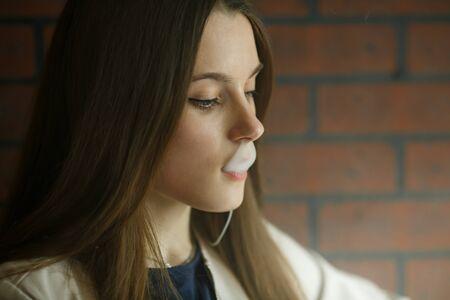 Vaping teenager. Young pretty white girl smoking an electronic cigarette in vape bar. Bad habit. Imagens