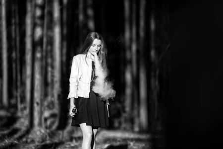 Vape teenager. Young cute girl in casual clothes smokes an electronic cigarette outdoors in the forest at sunset in summer. Bad habit that is harmful to health. Vaping activity. Black and white. Imagens