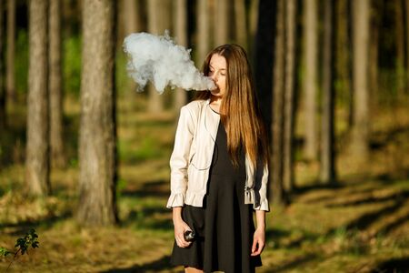 Vape teenager. Young cute girl in casual clothes smokes an electronic cigarette outdoors in the forest at sunset in summer. Bad habit that is harmful to health. Vaping activity. Imagens