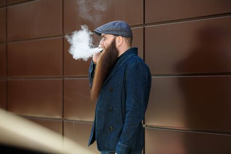 Vape bearded man. An adult man with a very long beard in a cap and sunglasses smokes an electronic cigarette and talkes on the mobile phone on a sunny day outside. Bad habit that is harmful to health Imagens