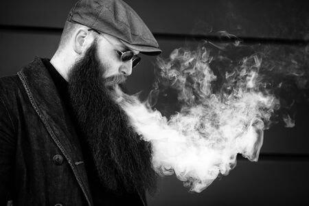 Vape bearded man. An adult man with a very long beard in a cap and sunglasses smokes an electronic cigarette on a sunny day outside. Bad habit that is harmful to health. Black and white. Imagens