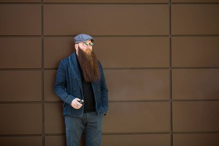 Vape bearded man. An adult man with a very long beard in a cap and sunglasses smokes an electronic cigarette on a sunny day outside. Bad habit that is harmful to health. Imagens