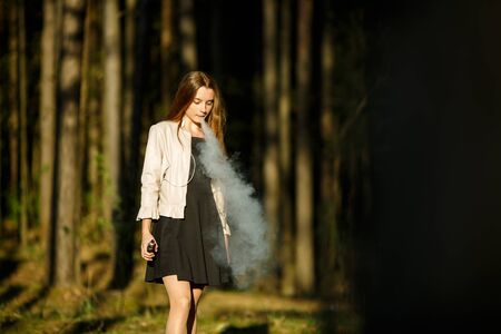 Vape teenager. Young cute girl in casual clothes smokes an electronic cigarette outdoors in the forest at sunset in summer. Bad habit that is harmful to health. Vaping activity. Banque d'images - 131557027