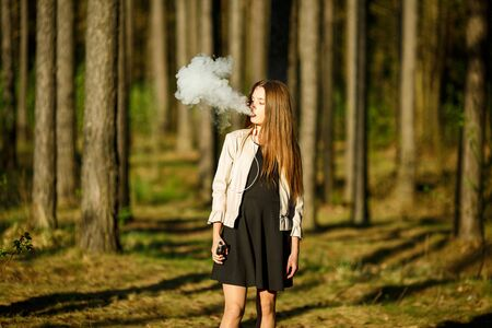 Vape teenager. Young cute girl in casual clothes smokes an electronic cigarette outdoors in the forest at sunset in summer. Bad habit that is harmful to health. Vaping activity. Banque d'images - 131557428