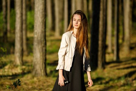 Vape teenager. Young cute girl in casual clothes smokes an electronic cigarette outdoors in the forest at sunset in summer. Bad habit that is harmful to health. Vaping activity. 免版税图像