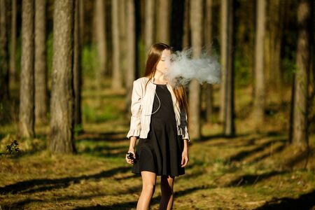 Vape teenager. Young cute girl in casual clothes smokes an electronic cigarette outdoors in the forest at sunset in summer. Bad habit that is harmful to health. Vaping activity. Banque d'images - 131557442