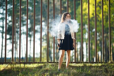 Vape teenager. Young cute girl in casual clothes smokes an electronic cigarette in front of a metal fence outdoors in the forest at sunset in summer. Bad habit. Stop vaping. Banque d'images - 133007914