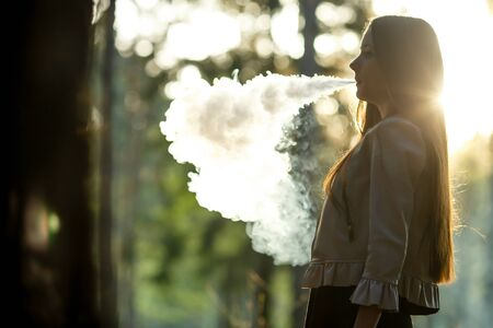 Vape teenager. Young cute girl in casual clothes smokes an electronic cigarette outdoors in the forest at sunset in summer. Bad habit that is harmful to health. Vaping activity. Banque d'images - 132013081