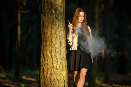 Vape teenager. Young cute girl in casual clothes smokes an electronic cigarette outdoors in the forest at sunset in summer. Bad habit that is harmful to health. Vaping activity. Banque d'images - 133007915