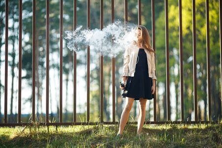 Vape teenager. Young cute girl in casual clothes smokes an electronic cigarette in front of a metal fence outdoors in the forest at sunset in summer. Bad habit. Stop vaping. Banque d'images - 132013699