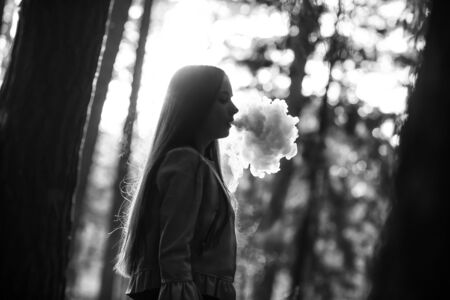 Vape teenager. Young cute girl in casual clothes smokes an electronic cigarette outdoors in the forest at sunset in summer. Bad habit that is harmful to health. Vaping activity. Black and white. Banque d'images - 132013589