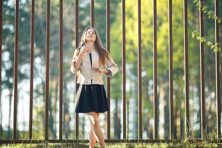 Vape teenager. Young cute girl in casual clothes smokes an electronic cigarette in front of a metal fence outdoors in the forest at sunset in summer. Bad habit. Stop vaping. Banque d'images - 132014229