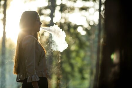 Vape teenager. Young cute girl in casual clothes smokes an electronic cigarette outdoors in the forest at sunset in summer. Bad habit that is harmful to health. Vaping activity. Banque d'images - 132013168