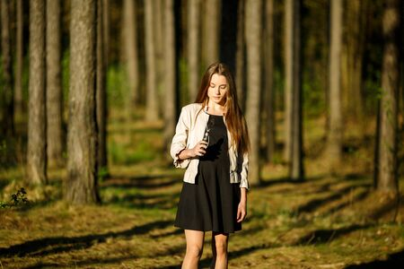 Vape teenager. Young cute girl in casual clothes smokes an electronic cigarette outdoors in the forest at sunset in summer. Bad habit that is harmful to health. Vaping activity. Banque d'images - 132013637